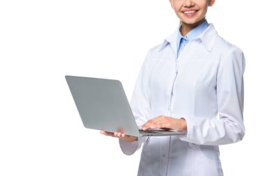 cropped view of female doctor in white coat using laptop, isolated on white
