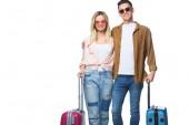 fiatal pár mosolyogva a bőröndök látszó-on fényképezőgép, elszigetelt fehér