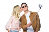 young couple taking selfie from monopod while woman kissing her boyfriend isolated on white
