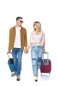 Fotografie young travelling couple holding hands and walking with suitcases isolated on white