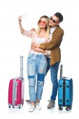young travelling couple with suitcases taking selfie with smartphone isolated on white