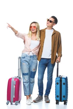 Young travelling couple with suitcases pointing somewhere isolated on white stock vector