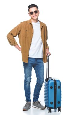 Handsome young man with luggage looking at camera isolated on white stock vector