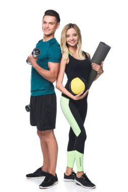 young sporty couple with various equipment looking at camera isolated on white