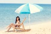 Fotografie atraktivní dívka v bílých bikinách s knihou na lehátko pod slunečníkem u moře