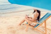 vonzó lány ül a strand szék kókusz koktél