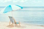 Fotografie slunce slunečník a plážová židle na písečné pobřeží u moře