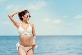 attractive young woman posing in sunglasses and white swimsuit near the sea on resort