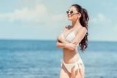 schöne Mädchen posiert in Sonnenbrille und Bikini in der Nähe des Meeres auf Resort