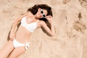 Fotografie top view of smiling girl in sunglasses and white bikini lying on sand