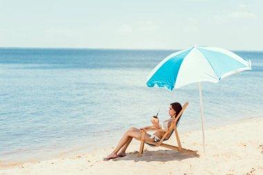 Beautiful girl in bikini with coconut cocktail resting on deck chair under beach umbrella near sea stock vector