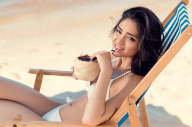 Beautiful girl in bikini drinking coconut cocktail on beach stock vector