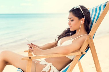 brunette girl listening music with earphones and smartphone while relaxing on beach chair near sea