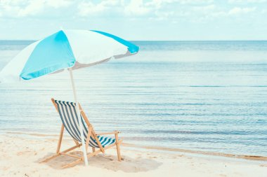 sun umbrella and beach chair on sandy shore near the sea