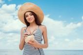 Fotografia ragazza attraente in cappello di paglia che tiene la noce di cocco verde con cannucce