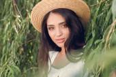 Fotografia Ritratto di ragazza attraente del brunette in cappello di paglia in posa vicino allalbero di salice