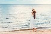 krásná dívka v bílých šatech, chůze na písečné pláži u moře