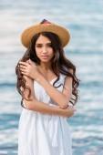 schöne junge Frau in Strohhut posiert am Meer