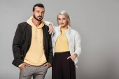 couple dressed in stylish autumn clothes posing isolated on grey background