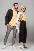young stylish couple posing in autumn outfits on grey background