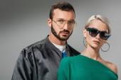 Módní pár pózuje v dioptrické brýle a sluneční brýle, izolované Grey