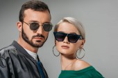 Photo fashionable couple posing in trendy sunglasses, isolated on grey