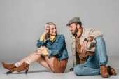 Fotografie stylish couple sitting in autumn outfit and looking at each other, on grey