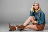 Fotografie schönes Modell in trendigem Cordrock und Jeansjacke auf dem Boden sitzend, auf grau