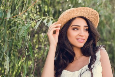 beautiful young woman in straw hat posing near willow tree