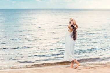 Beautiful girl in white dress walking on sandy beach near sea stock vector
