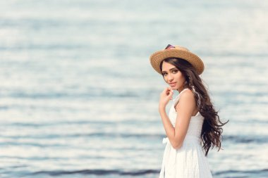 attractive brunette girl in straw hat and white dress walking near the sea