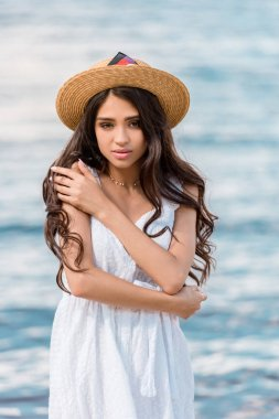beautiful young woman in straw hat posing near the sea
