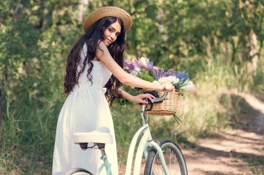 Beautiful young woman in straw hat posing with bicycle and flowers in wicker basket stock vector