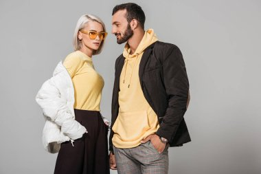 stylish couple of models in autumn outfits posing isolated on grey background