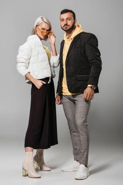 fashionable couple of models in autumn outfits posing on grey background