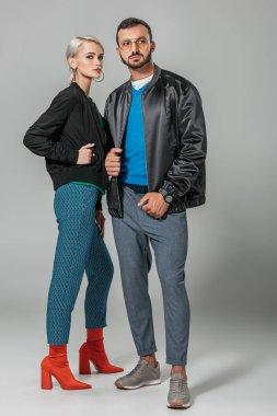 stylish couple of models posing in black jackets on grey background
