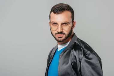 serious male model in stylish eyeglasses looking at camera isolated on grey background