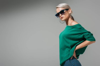 fashionable young woman in sunglasses posing with hands on waist isolated on grey background
