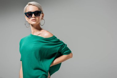çekici kadın modeli güneş gözlüğü ve gri arka plan üzerinde izole bel üzerinde el ile poz yeşil kazak
