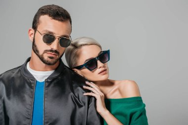 stylish couple posing in sunglasses for fashion shoot, isolated on grey