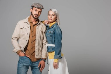 beautiful couple of models posing in autumn outfit, isolated on grey