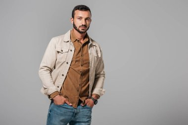 handsome man posing in corduroy shirt and autumn jacket, isolated on grey
