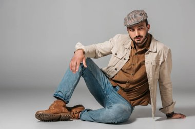 Bearded man posing in corduroy shirt, jeans and autumn jacket and tweed cap, on grey stock vector