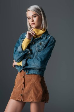 fashionable model posing in turtleneck, trendy corduroy skirt and jeans jacket, isolated on grey