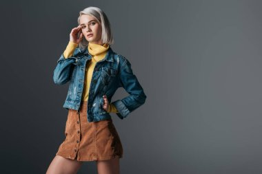 woman posing in yellow turtleneck, trendy corduroy skirt and jeans jacket, isolated on grey