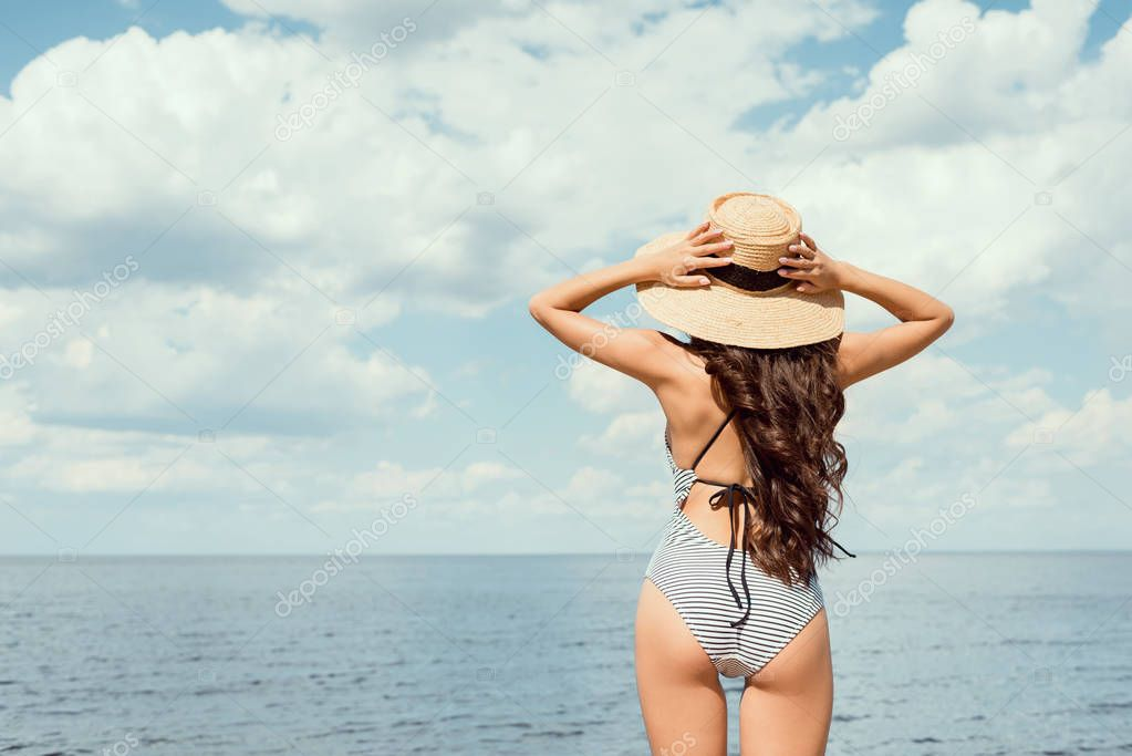 back view of girl in swimsuit and straw hat looking at sea