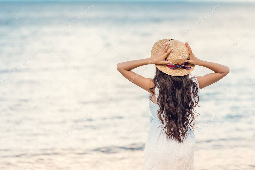 back view of girl in straw hat looking at sea