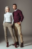 young couple posing in stylish autumn outfit, on grey