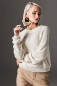 attractive elegant woman posing in white sweater and big earrings, isolated on grey