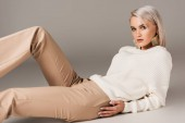 Photo elegant blonde woman lying in white sweater and beige pants, on grey